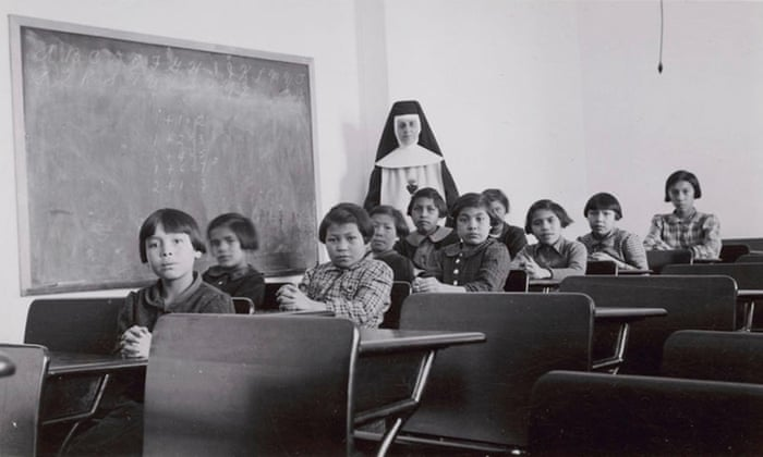 A group of female students and a nun pose in a classroom at Cross Lake Indian Residential School in Cross Lake, Manitoba in February 1940. Photograph: Reuters