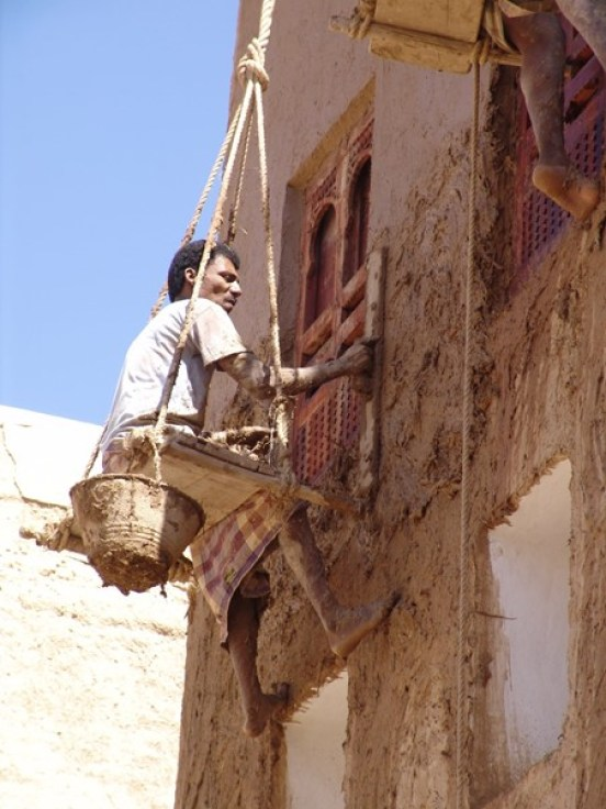 A man in traditional clothing is suspended from a rope against one of the 500-year-old skyscrapers, applying mud to maintain it it