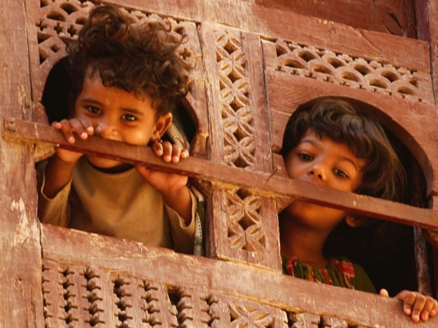 Two curly-haired children peering out of a traditional wooden Yemeni carved window into the street below in Shibam