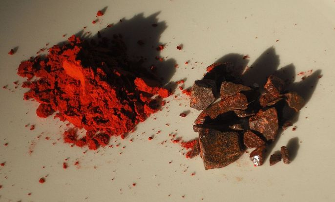 red dragon blood powder and brownish crystals next to each other on a white background