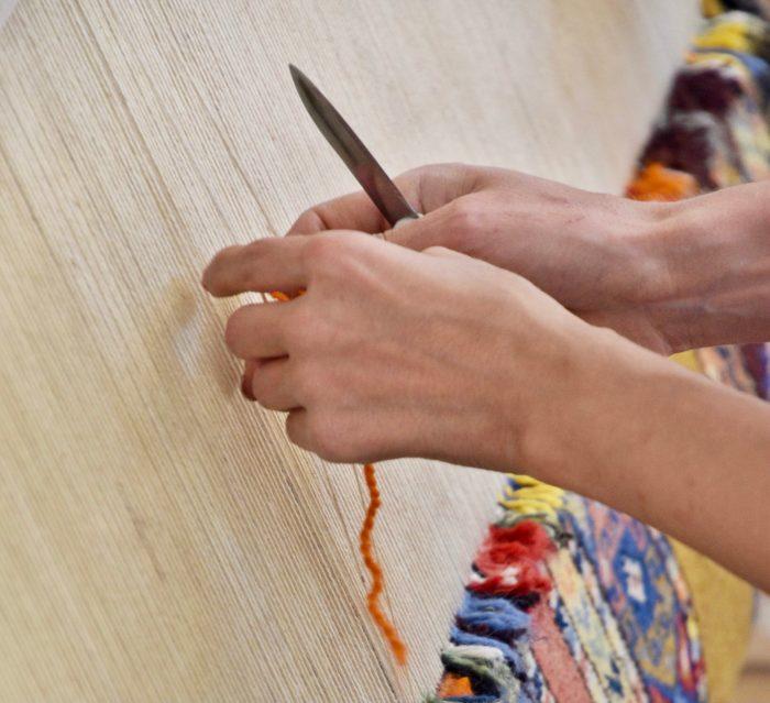 Hands knotting the orange yarn on a rug loom