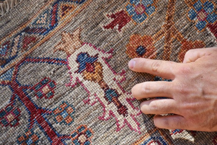A hand points to a motif on a knotted Turkish carpet. Prominent colors are gray, blue, red, orange, tan, and white.