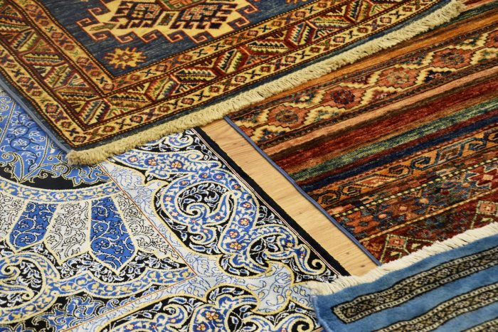 Intricate swirl and block designs on four overlapping rugs. Primary colors are blue, creme, yellow, and orange.