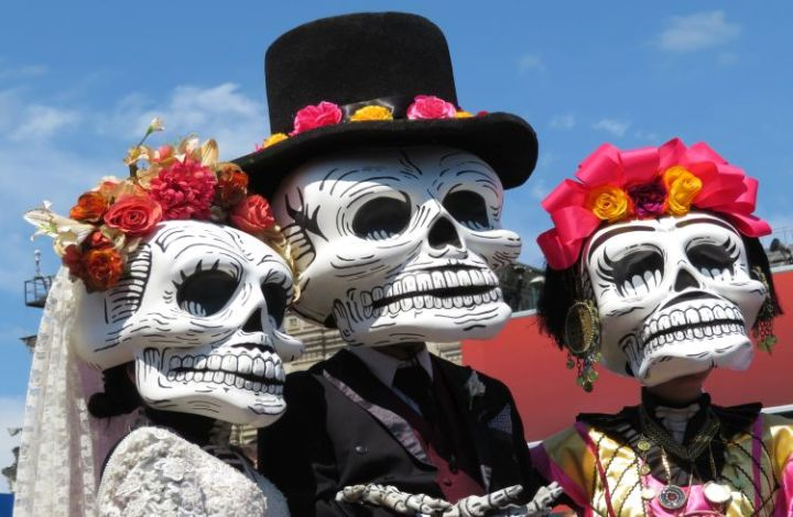Three people in costume wearing large skull heads with flowers wreathed on their crowns and the middle one wearing a black top hat and suit.
