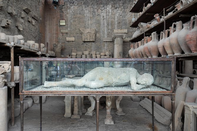 A stone room where a clay mould of a mans body lies within a glass case and the walls are filled with shelves holding earthen pots and vases.