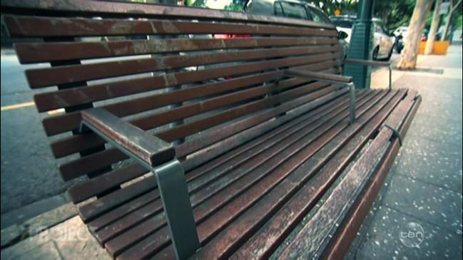 A wooden park bench separated by metal arm rests