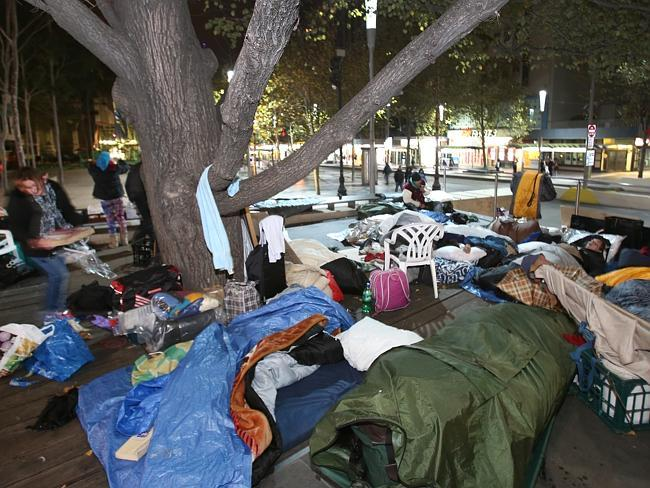 A large group of homeless people sleep in sleeping bags under a tree