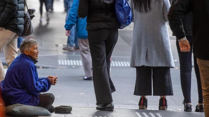 A professional begger on the side of the street cups his hands for money as people pass by