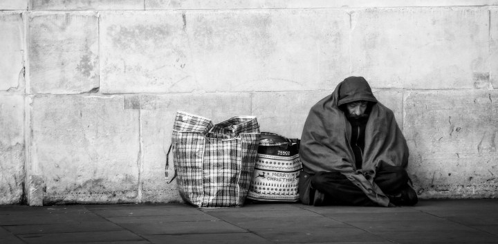 Black and white shot of a homeless man cloaked in a blanket with a large bag next to him and a concrete wall behind him