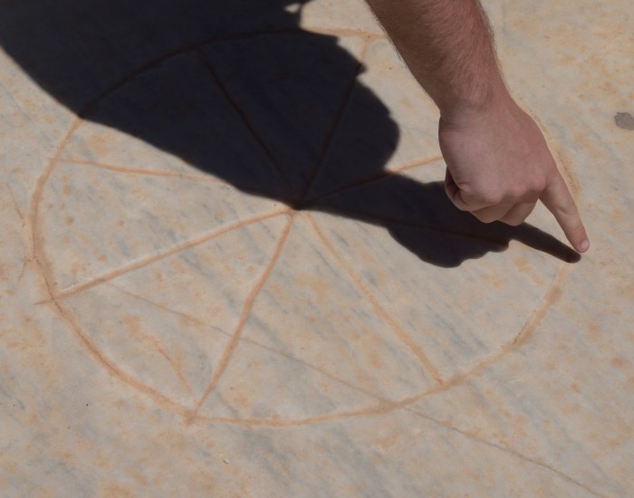 An engraved circle in stone outside the theater in Ephesus. It has 8 lines cutting through the middle. A finger points to the rim of the circle.