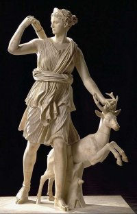 A chiseld stone stateue of tehe goddess Artemis, who is besides a deer.