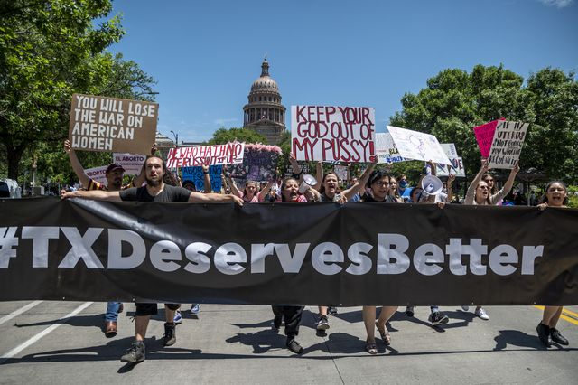 People protest on the road holding a large sign that says '#TXdeservesbetter'