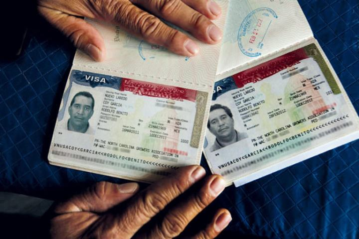 The photograph portrays two American H-2A visas of Mexican agricultural employees.