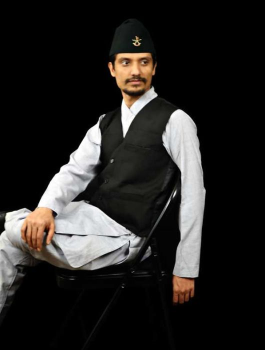 Image of a tarditional Nepali outfit. The outfit is a grey color set with a black suit vest.