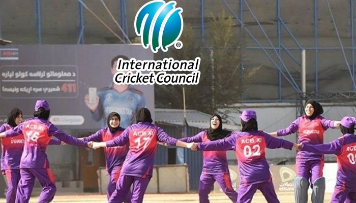 A group of Afghan female cricket players dressed in purple hold hands and form a circle