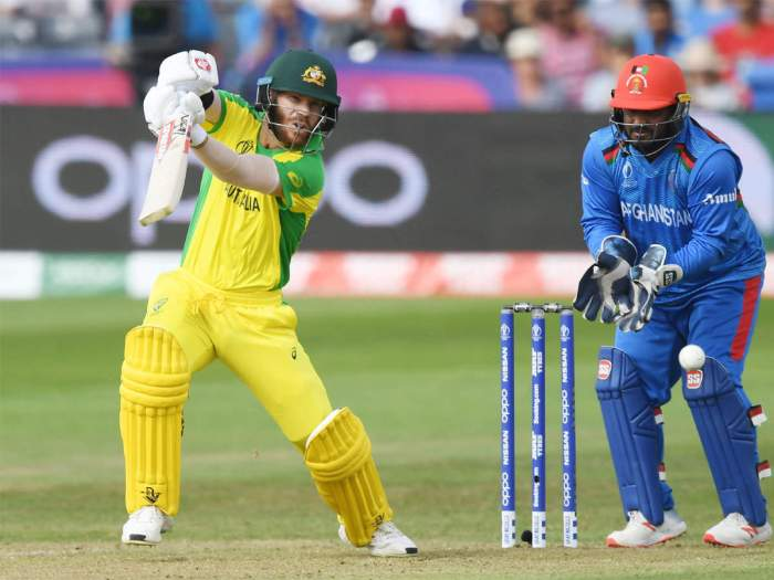 An Australian man dressed in yellow bats a cricket ball next to a blue Afghan player standing behind the stumps