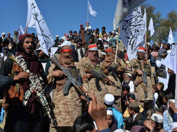 Members of the Taliban dressed in army clothes stand in a line holding guns with people holding flags around them