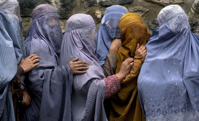 Four Afghan women huddled in a line and draped in blue head and body coverings, one woman in the middle wears orange