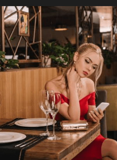 A lady dressed in a red dress at a restaurant.