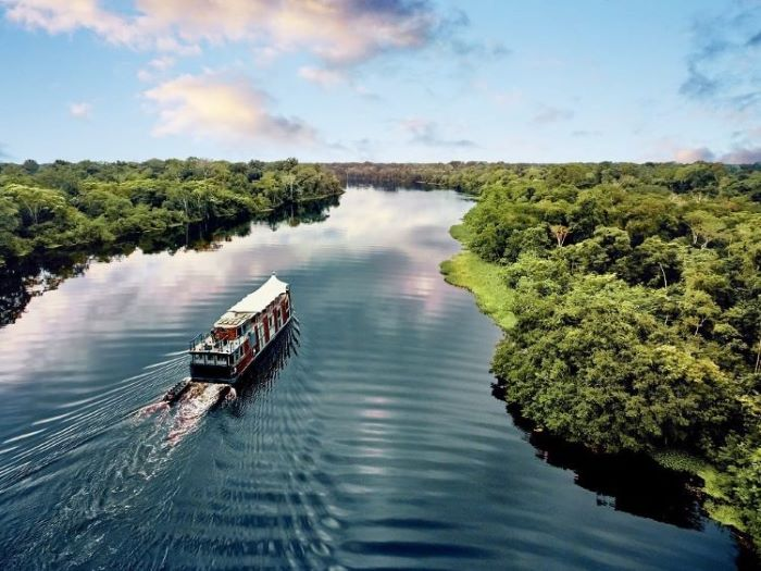 Cruise ships on the Amazon river in Peru floating around the greenery