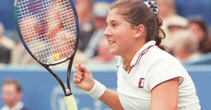 Monica Seles in 1995 playing a tennis match. She is holding a tennis raquet.