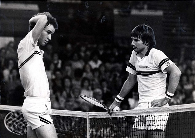 John McEnore and Jimmy Connors conversing on the court. The net separates the two. The photo is in black and white.