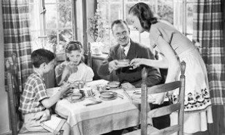 The photograph of a 'picture perfect family' at a breakfast table. A wife is handing a plate to her husband while smiling at her two kids- a boy and a girl- who are eating her meal.