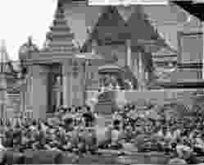 A black and white photograph of the King of Siam and his procession in the front of the palace and in the middle of his people, who are sitting on their legs with their back straight and their heads facing their king.