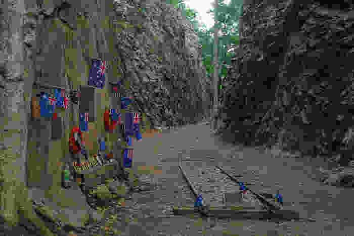 A colour photograph of the memorial by Australians and New Zealanders for those they lost in the Hellfire Pass, with tokens of appreciation and their countries flags on the wall and on the small part of the railway that remained.
