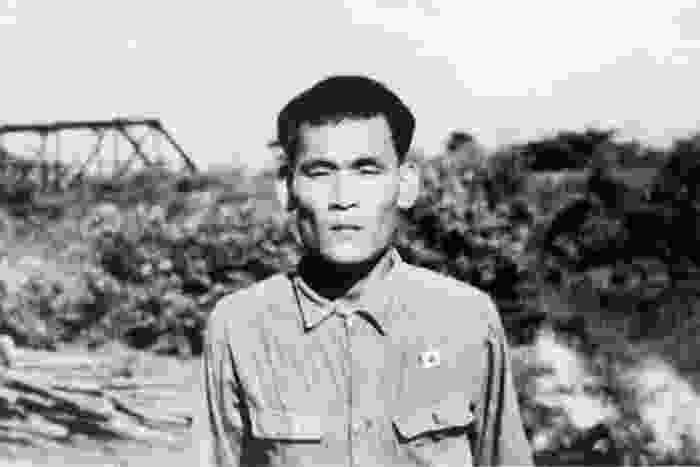 A black and white photograph of Seiichi Okada in Siam, standing in front of a forest in Thailand.
