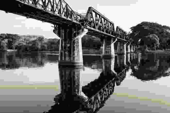 A black and white photograph of the Bridge on the River Kwai in present day, with the river so clear there is a disitinct reflection of it.