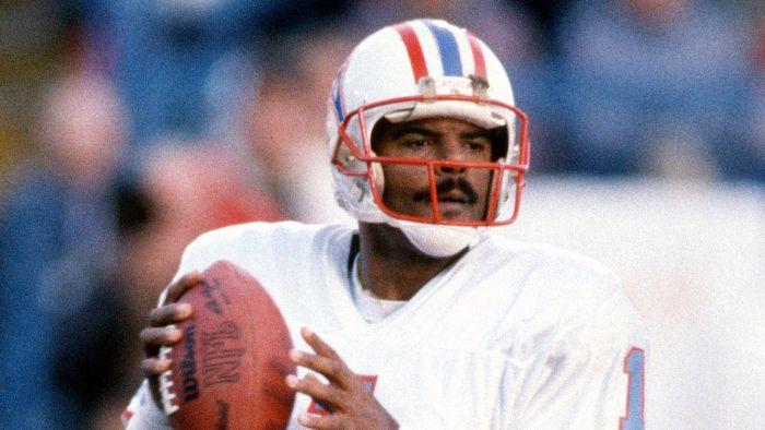 Warren Moon holding a football. He is wearing a Houston Oilers jersey and helmet.