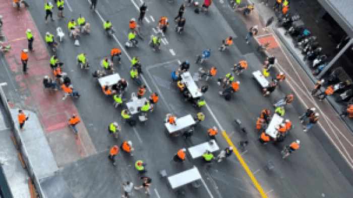 Birds-eye-view of construction workers wearing hi-vis gear sitting at white tables in the middle of a city road