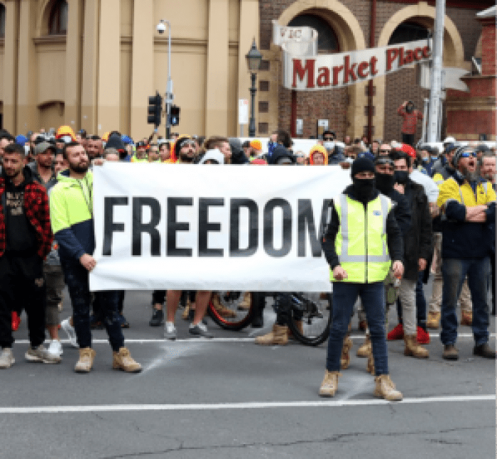 Protesters gather outside a biege market bulding holding a 'freedom' sign