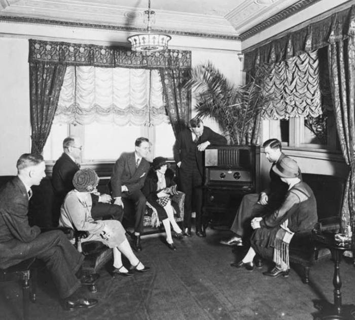 A group of people listening to the radio. The picture is in black and white and was likely taken in the 1930s.