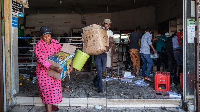 a colored image of a woman in her pink dress and a boy carrying boxes out of the  looted store as other men at the back are collecting stuff from the store