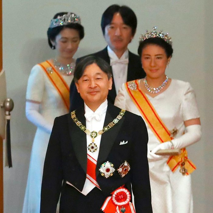 A photograph of the current Emperor and Empress of Japan entering a room in their formal attire, followed by the Crown Prince and Princess of the Imperial Family.