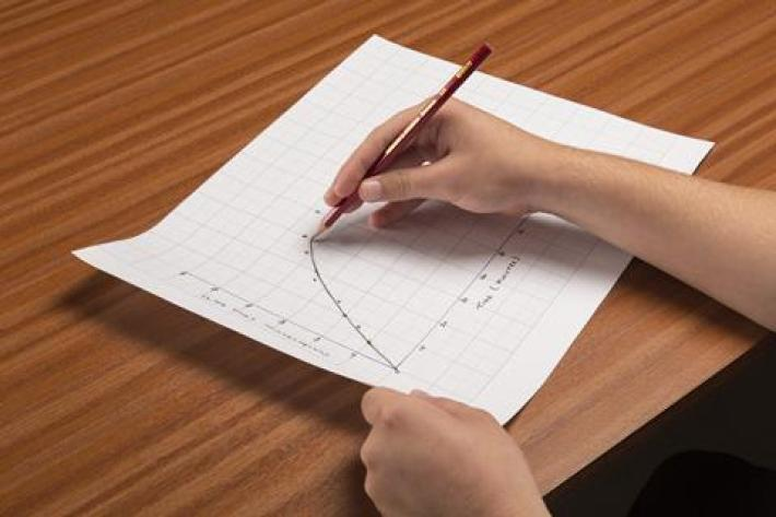 A photo of a hand plotting a curve on graph paper