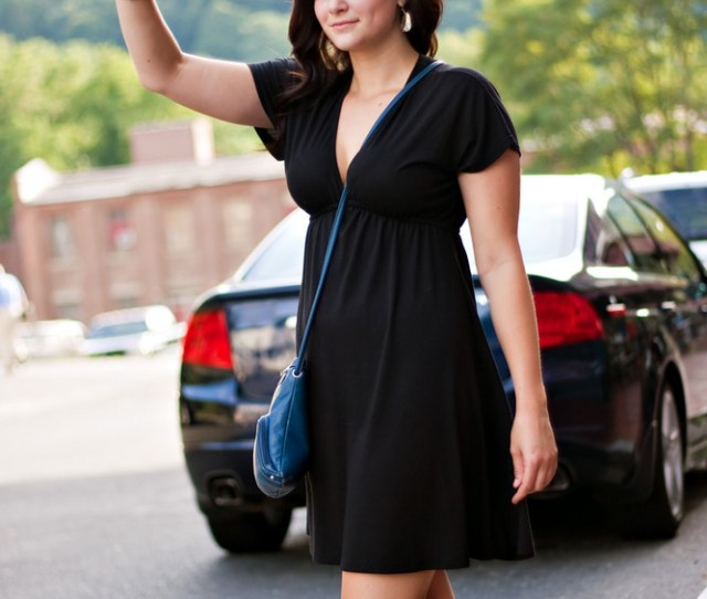 A Gorgeous Brunette Woman Hails A Cab At The Side Of The Road In The City