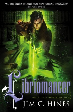 A young white man with dark hari is pulling a space weapon out of a book. There are full bookshelfs as well as piles of books in the background. Title: Libriomancer. Author: Jim C. Hines.