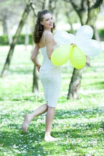 Young Woman Walking Barefoot In Meadow Holding Balloons