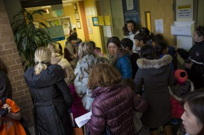 Parents flood the entrance of the Russian School of Mathematics in Newton to drop off their children before the Math Kangaroo competition. (Jesse Costa/WBUR)