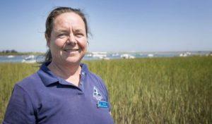 Mass Audubon's Liz Duff stands in the salt marsh off Conomo Point Road in Essex. (Robin Lubbock/WBUR)