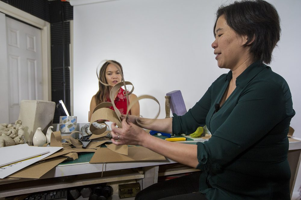 Art Prof's Clara Lieu shows her teaching assistant how to create a sculpture with chipboard. (Jesse Costa/WBUR)