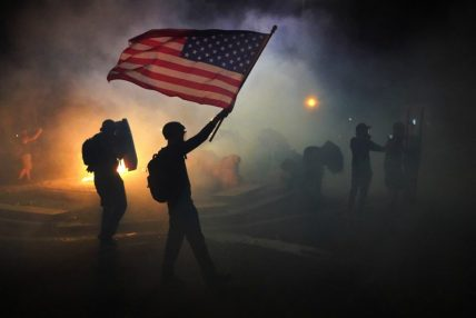 A protester flies an American flag while walking through tear gas