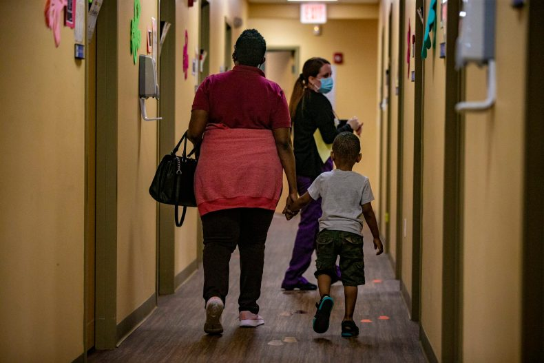 Medical assistant Keyla Santiago-Rivera leads a mother and child to an examination room at Brockton Neighborhood Health Center. (Jesse Costa/WBUR)