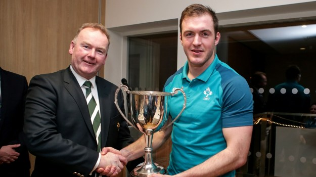 Victorious Ireland captain Niall Kenneally is presented with the Dalriada Cup by IRFU Committee member Michael Collopy ©INPHO/Laszlo Geczo