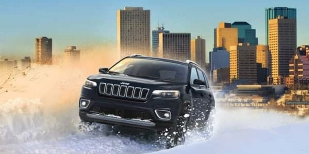 A black 2019 Jeep Cherokee driving through a snowdrift in the Edmonton river valley, the city skyline in the background