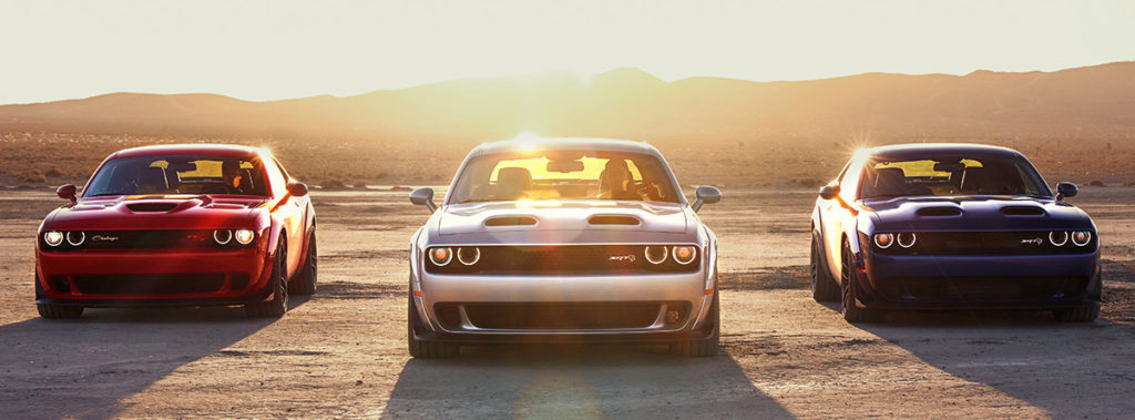 three dodge challengers out in the desert