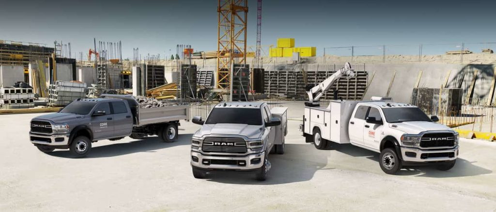 Three new 2019 Ram Chassis Cab vehicles parked in a large construction site.